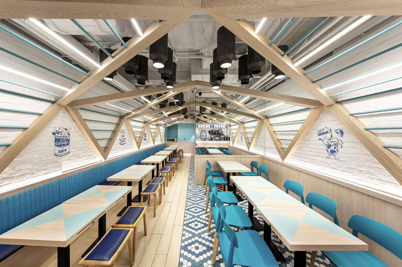 Atelier E have completed this modern restaurant design filled with blues and wood, was inspired by elements found in a traditional dairy farm, like a pitched roof and milk cans.