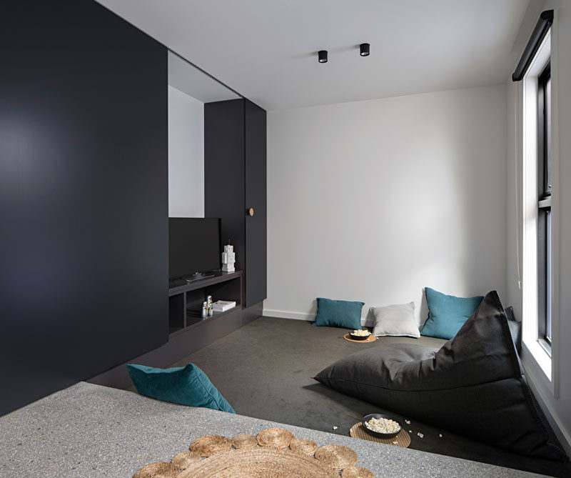 This modern house has a media room with a TV pit. The television is hidden behind an oversized matte black sliding door, and to watch the tv the kids have to close the door, therefore creating a closed-off space to enjoy their show as their parents enjoy peace and quiet in the main living area of the house.
