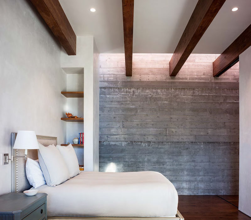 In this modern guest bedroom, the concrete and white walls are broken up by the use of dark wood beams, shelves and flooring.