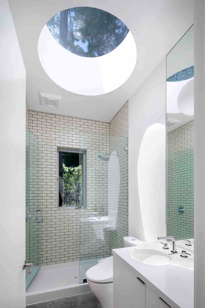 In this modern bathroom, a large circular skylight adds a lot of natural sunlight to the space, while the white walls and white vanity have been paired with a cream-colored rectangular tile to help reflect the light. A glass shower door keeps the rest of the room dry, and a small window lets you look out into the trees as you are showering.