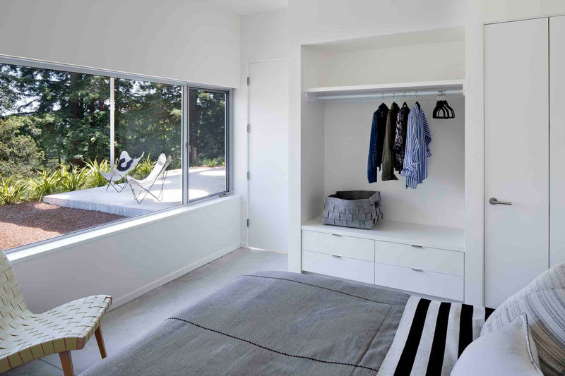 This modern guest bedroom has a large window to provides view and natural light to the room, and a built-in open closet is a great space for guests to hang their clothes.
