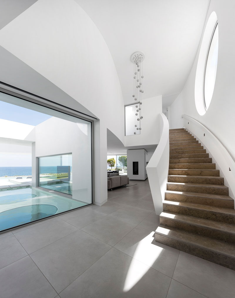 Inside this modern house with a white interior is a curved staircase with a large circular window that leads you to the upper level of the home.