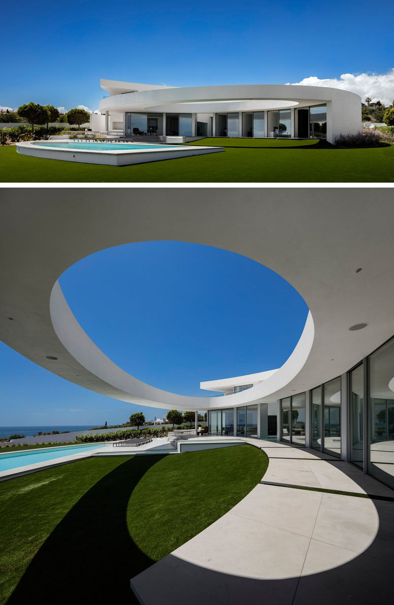 This modern sculptural house has a large landscaped backyard that's home to a swimming pool and tiered outdoor patio area, set up for lounging. A large ellipse cut out in the house design adds a sculptural touch.