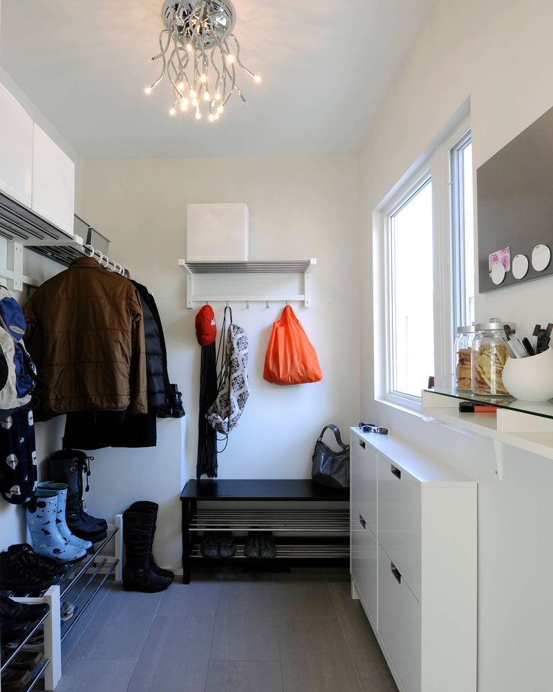 In this mostly white modern mudroom, there's plenty of shoe storage in the form of shoe racks, while above them are spaces to hang coats. Thin wall mounted cabinets under the window give each family member a place to store bits and pieces, and white cubes and metal bins on top of the hanging racks create extra storage space. A little shelf is home to containers of snacks and pens, and a magnet boards lets family members leave notes for each other.