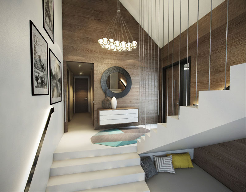 Inside this modern house, the wood walls create a natural warmth to the entryway, and white stairs direct you to the different areas of the home.