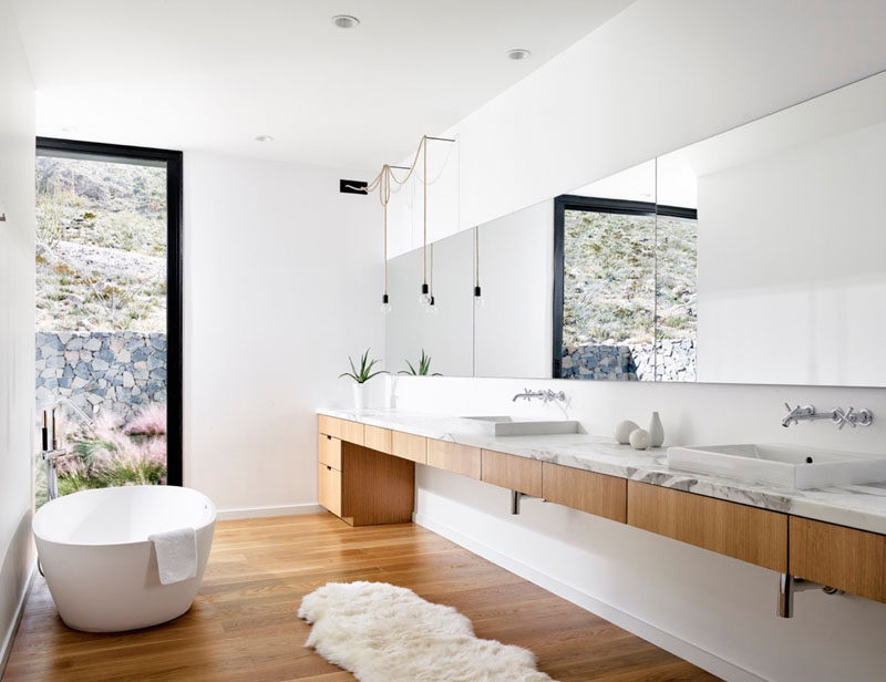 In this modern master bathroom, white walls, a white oak vanity and matching floors, a white stand alone tub, and marble countertop give the bathroom a sophisticated and luxurious feel that's bright and airy.
