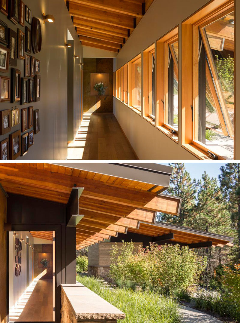 In this modern vacation home, a bright hallway, lined with windows and family photos, leads away from the main living area into the private spaces at the back of the cabin, and also leads back outside and connects to a path that runs around the exterior.