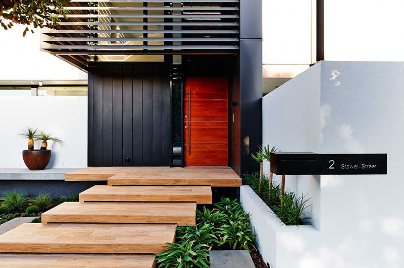 This large wood door, made up of four rich wood panels and a silver metal door handle, warms up the black metal panels and creates a contemporary look on the exterior of this Australian home.