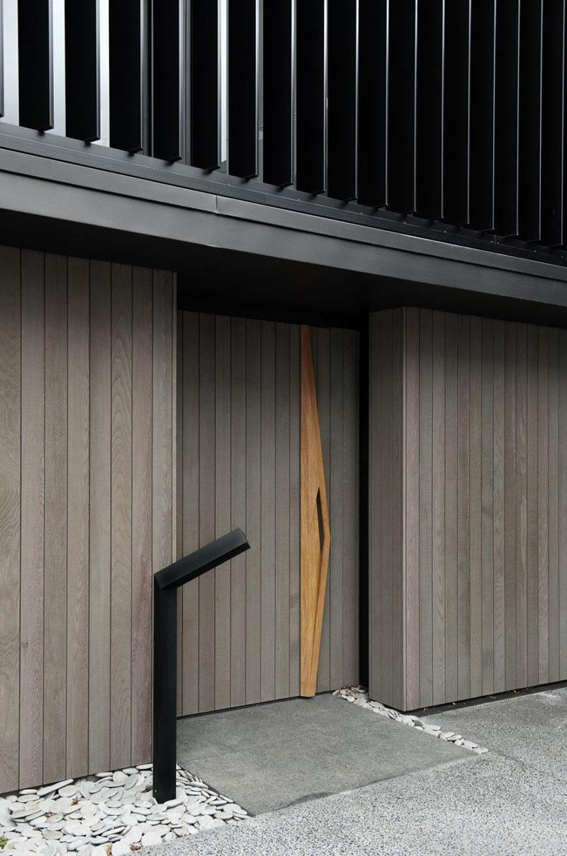 The vertical grey wood panels of this wood front door are interrupted by a sculptural door handle that runs the length of the door.