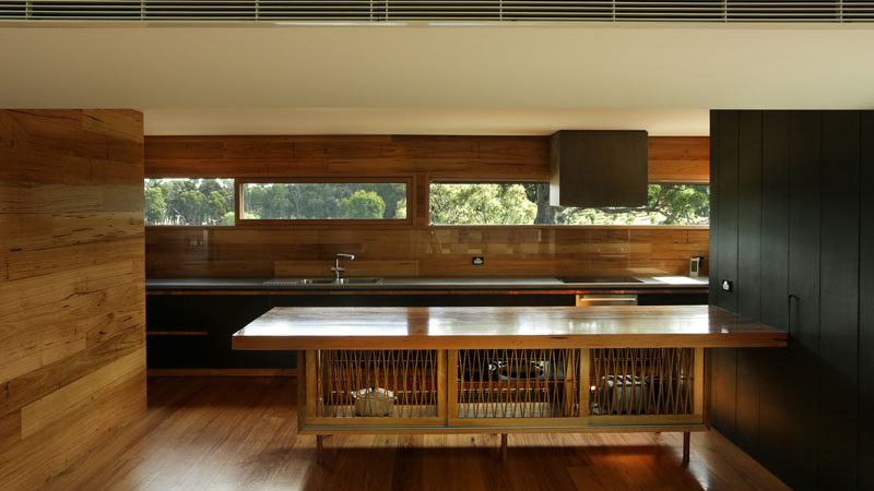 In this wood-clad kitchen, the large island features artistic doors and black wood cabinets add a modern touch to the room, while a letterbox window along the back wall connects the kitchen to the outdoors.