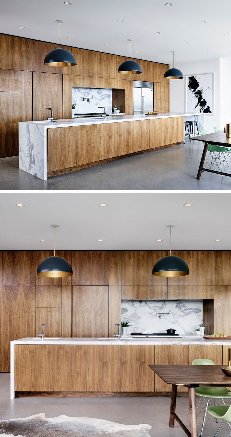 Polished concrete floors together with white walls give this kitchen a modern, clean feel that's warmed up by the American black walnut covering the cabinets on the wall and on the island. The marble countertops and backsplash add a luxurious touch to the warm wood, and pendant lighting above the island helps brighten the space once the sun goes down.