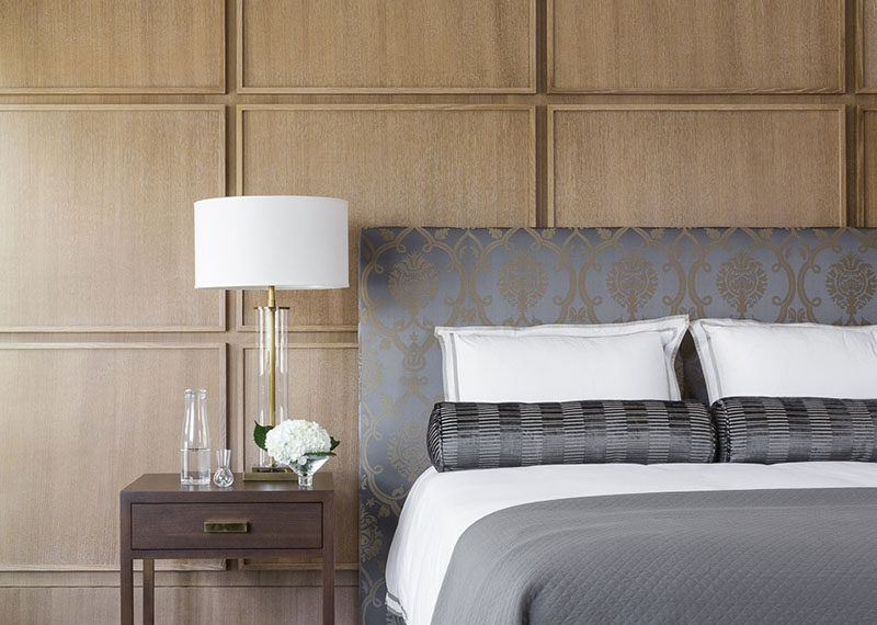 This contemporary bedroom uses square wood panels to create a modern accent wall behind the bed.
