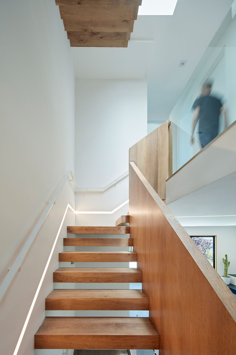 These modern wood stairs have a small light built into the wall that runs the length of the stairs.