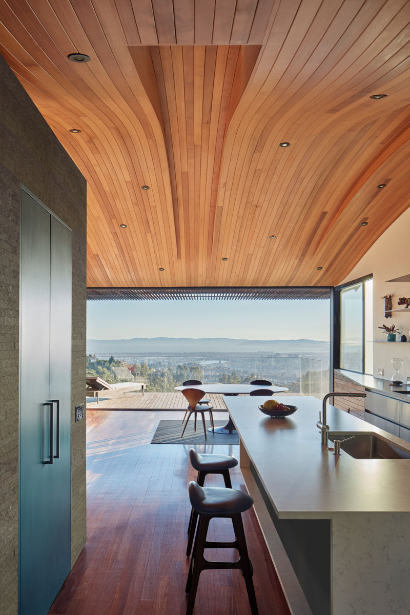 This modern home has a curved wood ceiling with the long sections of wood helping to elongate the interior and draw your eye to the balcony and view.