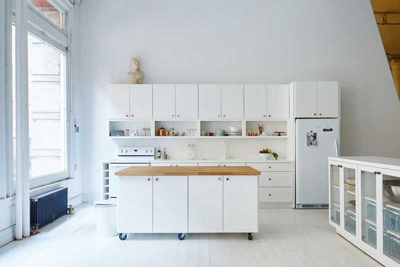the wheels on the bottom of this movable white kitchen island with a wood countertop lets people move it around so they can prep things closer to the rest