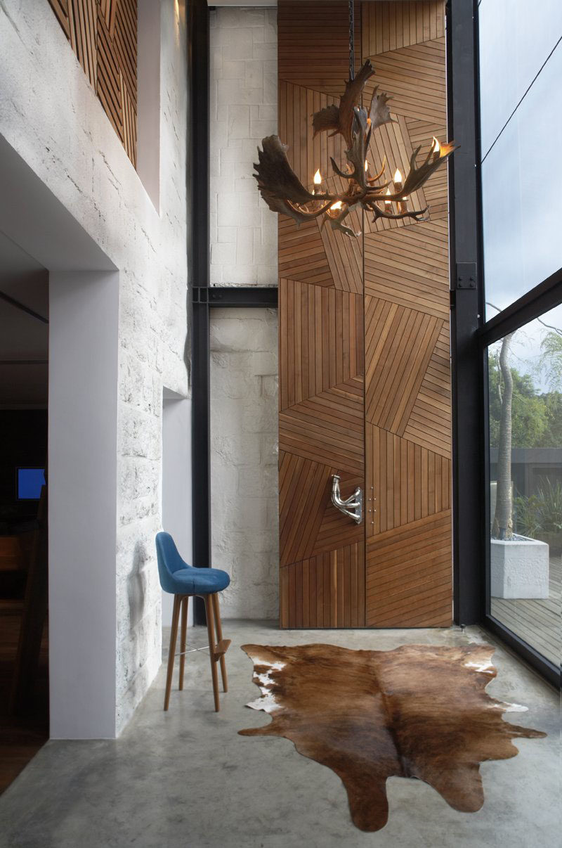 Light wood strips arranged in a geometric fashion make up these 23 foot tall doors that lead into the study of the home, while sculptural metal door handles help you pry the doors open.