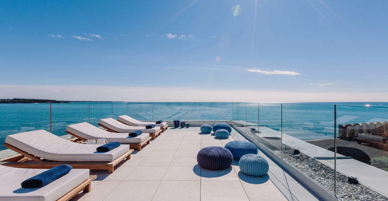 Glass panels surrounding this large rooftop deck filled with daybeds, to ensure that the views are never interrupted and that the sea breeze never gets in the way of rooftop sunbathing.