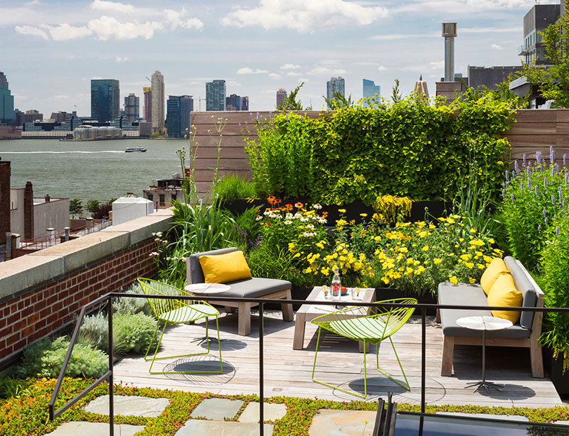 The rooftop of this New York warehouse turned residence has a lush garden filled with flowers and a cozy lounge area that provides an escape from the hustle of city living.