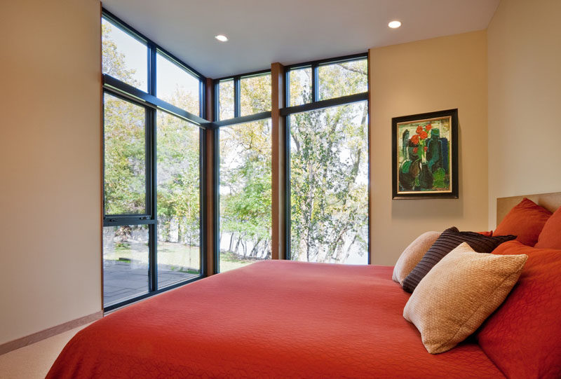 Large floor to ceiling windows in this modern bedroom let in lots of natural light and take advantage of the lakeside views at all hours of the day.