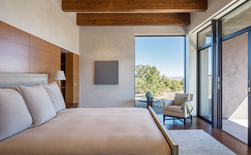 In this simple master bedroom, large windows provide picturesque views of the surrounding landscape, and sliding glass doors allow the home owner to enjoy the porch directly from their bedroom.