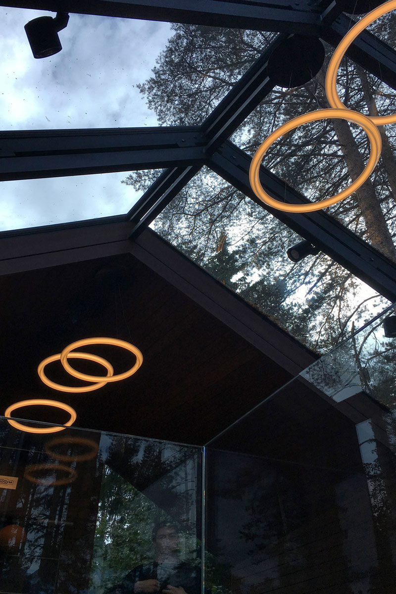 In this modern yoga studio, circular lights as well as a ceiling of windows ensures that the space is bright and that views of the forest can be seen when working out.