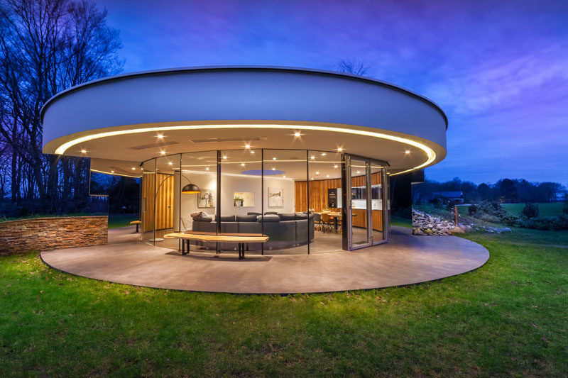 Located in an opening in a Dutch forest, this small, circular modern house was designed for a couple and their dogs. The circular house features curved windows that wrap around the front of the home and mirrors at each end give the appearance that the windows never end.