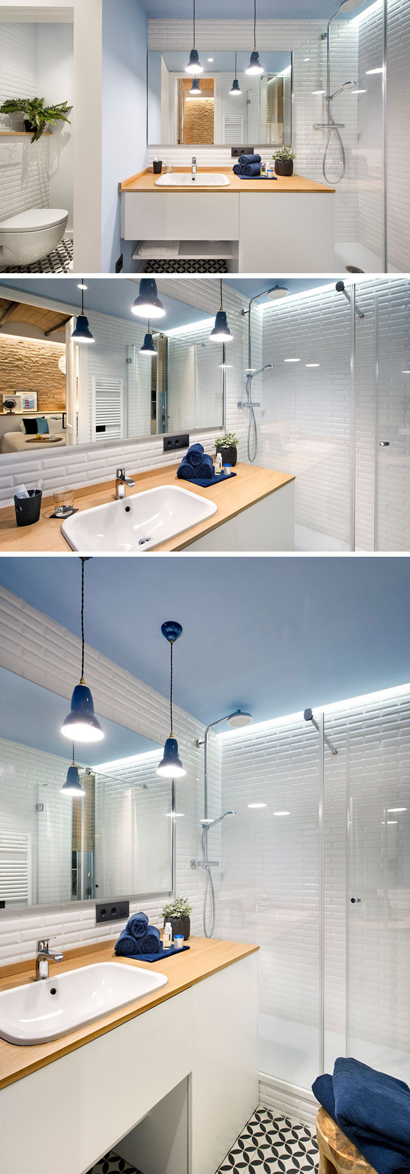 In this small modern bathroom you'll find white tiles and cabinetry, light blue walls and ceiling, and a wood countertop matches the palette of the rest of the apartment. Hanging pendant lights above the sink brighten the space and make it more inviting and plants in the bathroom create a natural vibe and bring a touch of life into the space. The shower is separated from the rest of the bathroom with a glass shower surround.