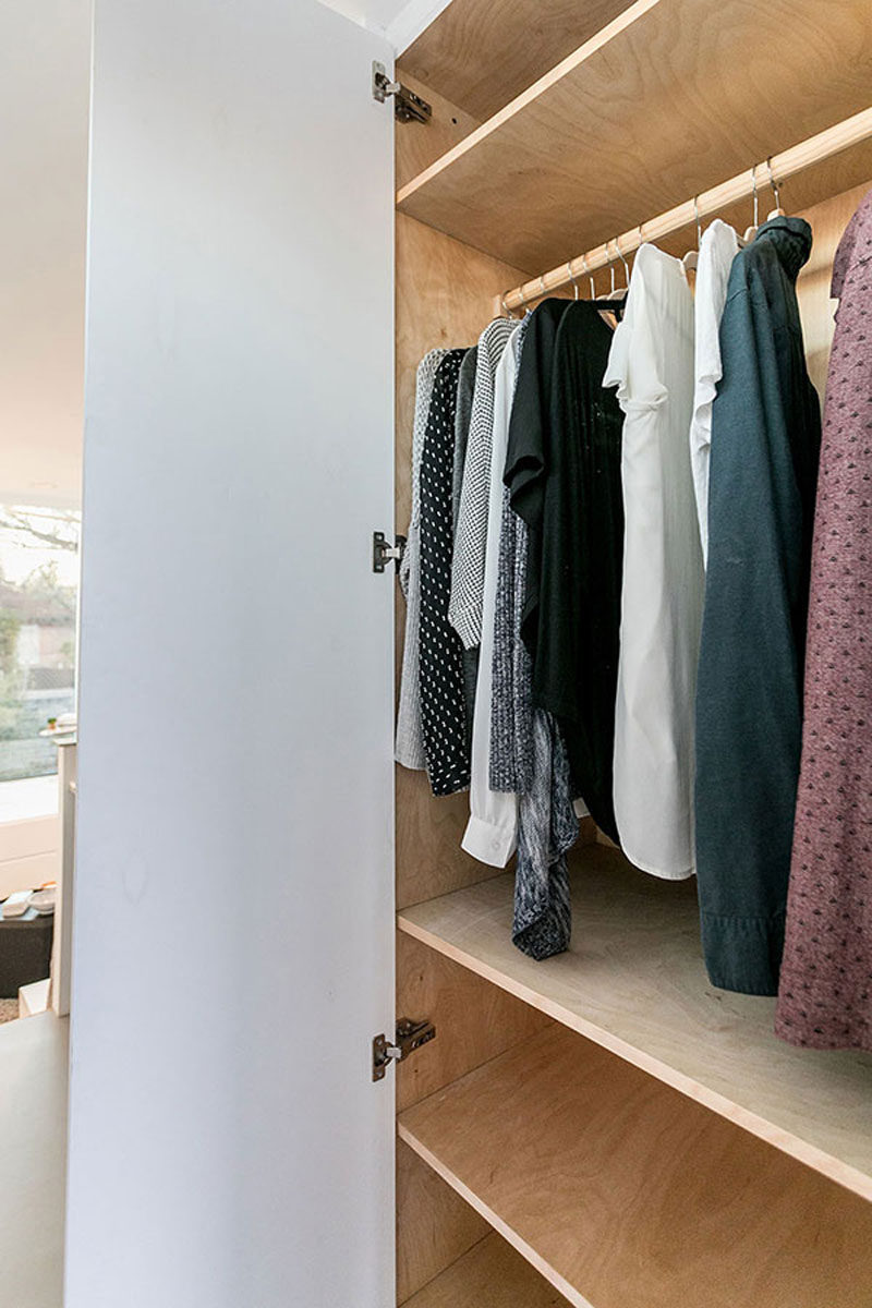 In this modern tiny house, there's a storage closet that has a bar for hanging clothes and plenty of wood shelves.