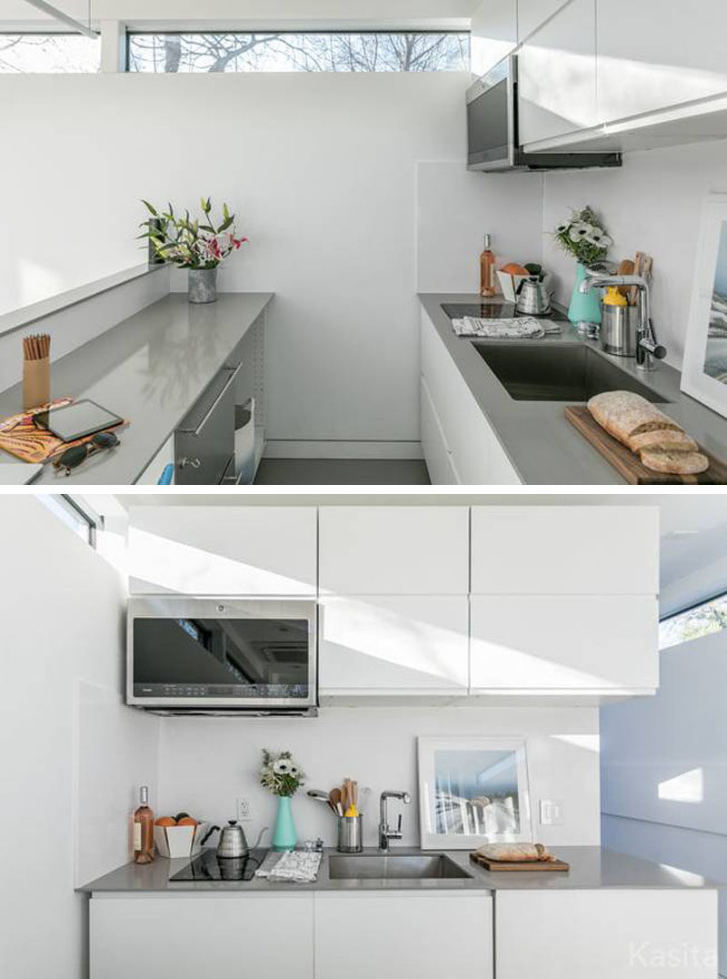 This small white and grey kitchen has a two burner induction cooktop and a convection microwave oven, as well as more storage and two counter spaces.  #TinyHouse #TinyHome #Architecture #SmallLiving #ModernTinyHouse #SmallHouse #TInyHouseKitchen