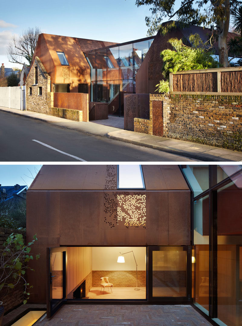 This home, built behind a 19th century stable wall, has a modern look to it created by the use of large glass panels and perforated weathering steel covering the exterior.