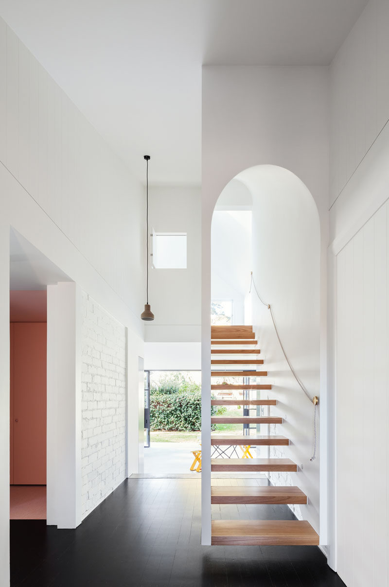 A white arched wooden staircase leads up to the second story of the extension of this renovated house.