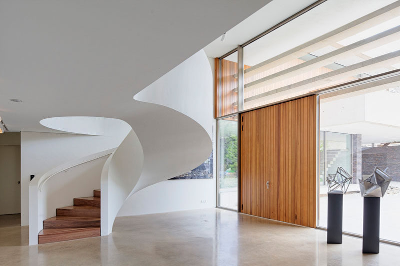 This white modern spiral staircase features a white railing and wood steps to keep the design clean and simple.