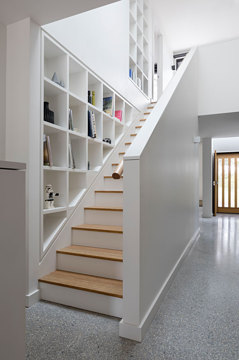These white and wood stairs are lined with custom-designed shelving to display personal items, while the skylight above gives off plenty of natural light.