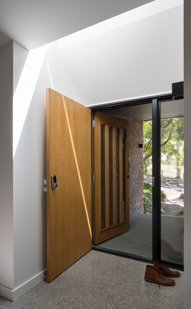 In the entryway of this modern house, a skylight is positioned directly above the wooden front door lets natural light to fill the space.