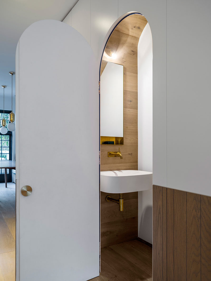 In this modern house, there's a hidden powder room with an arched door located under the stairs.
