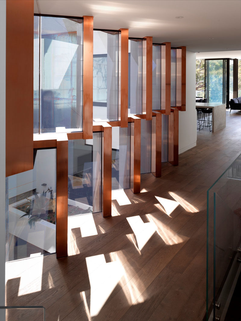 This modern hallway overlooks a landscaped courtyard, while sculptural copper fins filter the light.