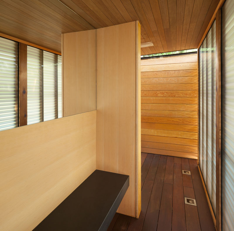 This modern pool house has a change room and shower, with frosted glass and wood slats providing some privacy.