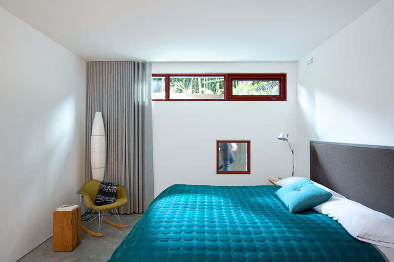This modern bedroom has bright white walls, multiple small windows and a bright blue blanket on the bed for a pop of color.