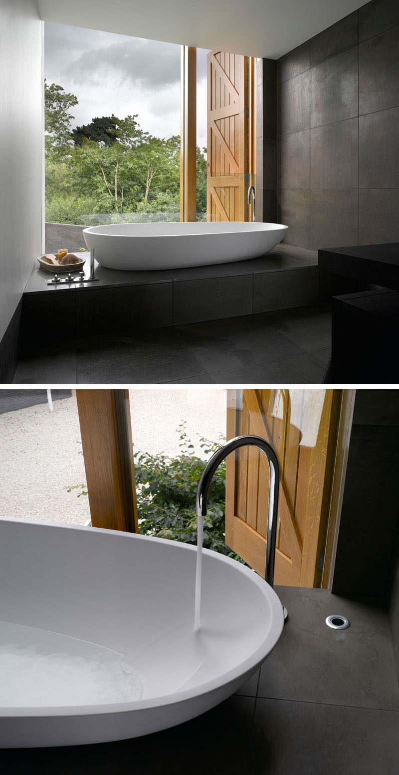 In this master bathroom, dark tiles have been paired with white walls and bathtub for a minimalist look, while the large windows provides views of the garden.