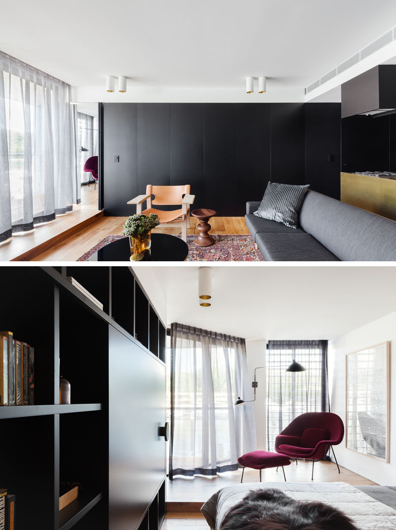 Hidden within a wall of black cabinets in this apartment is a door that leads to the bedroom. Inside the bedroom, there's a raised platform with a comfortable chair for relaxing and watching the boats outside.