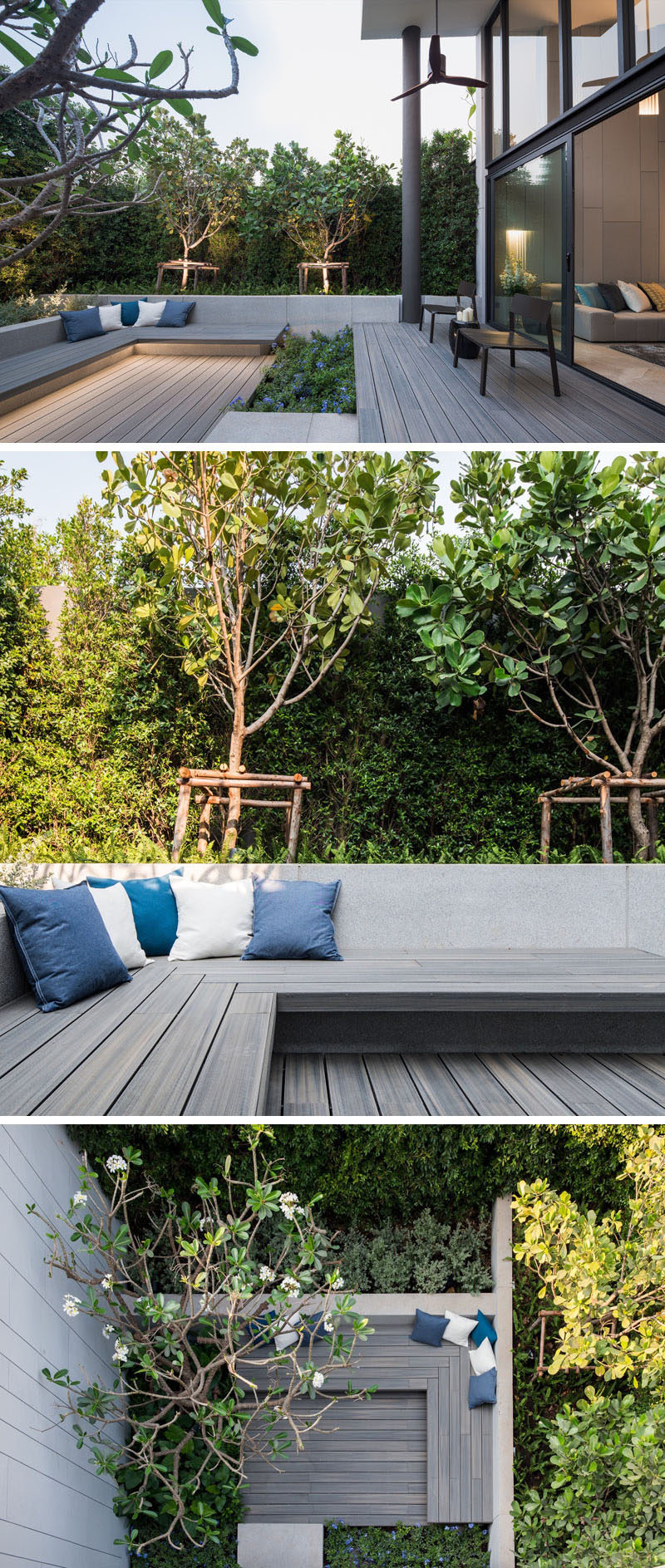 This small and modern backyard has a small path that connects the patio to a larger seating area with built-in wood benches and hidden lighting, that's surrounded by plants.
