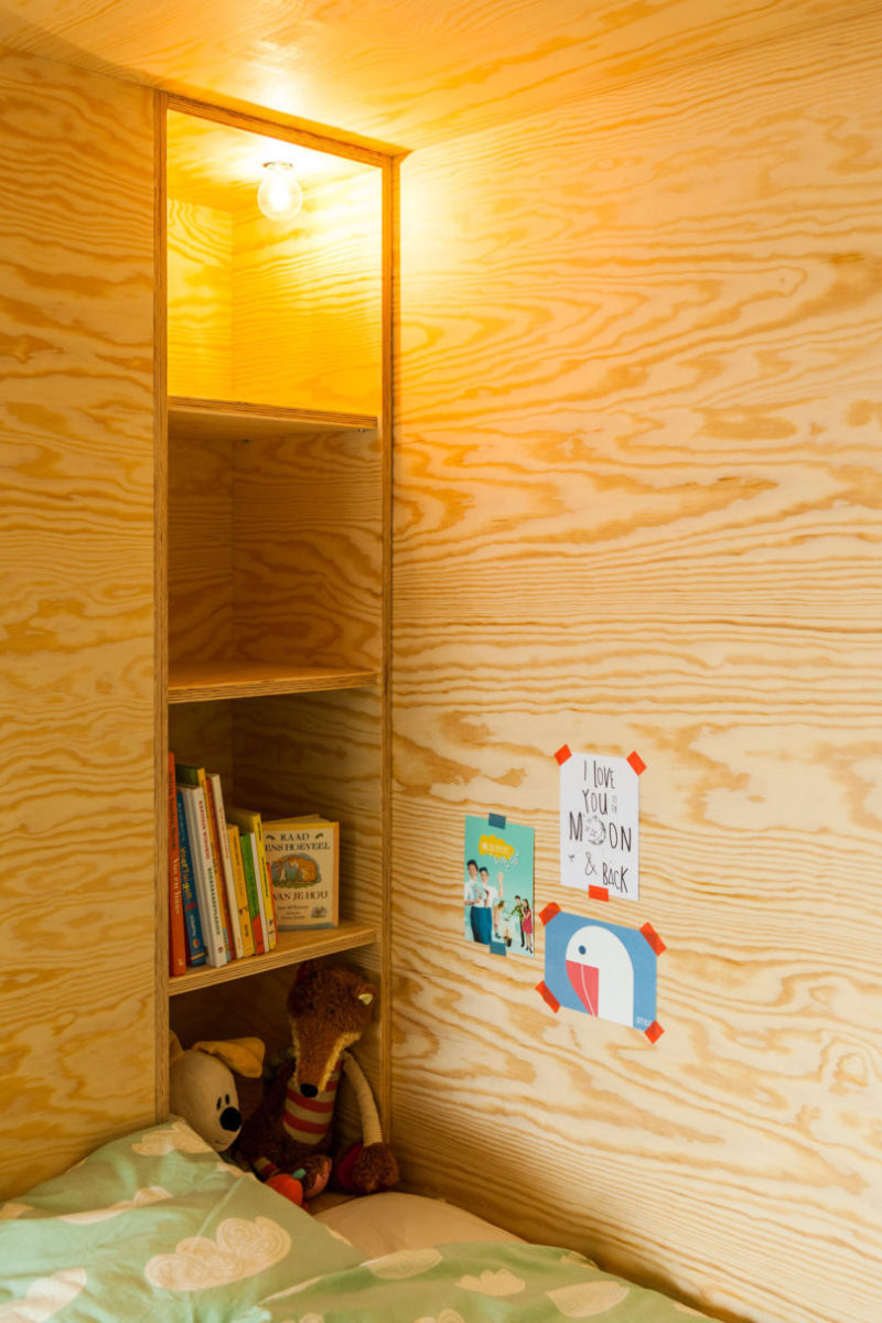 Wooden shelving sits beside this kids bed, and acts as a place for books and toys.