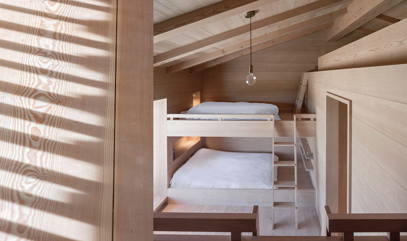 This modern Scandinavian inspired bedroom features built-in bunk beds and a small loft area.