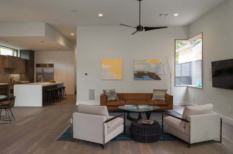 This modern house has an open floor plan, with the living room, dining room and kitchen all sharing the space. A window wrapping around the corner provides natural light to the living room.