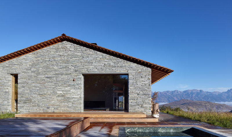 This modern stone and wood house has a deck with a built-in spa.