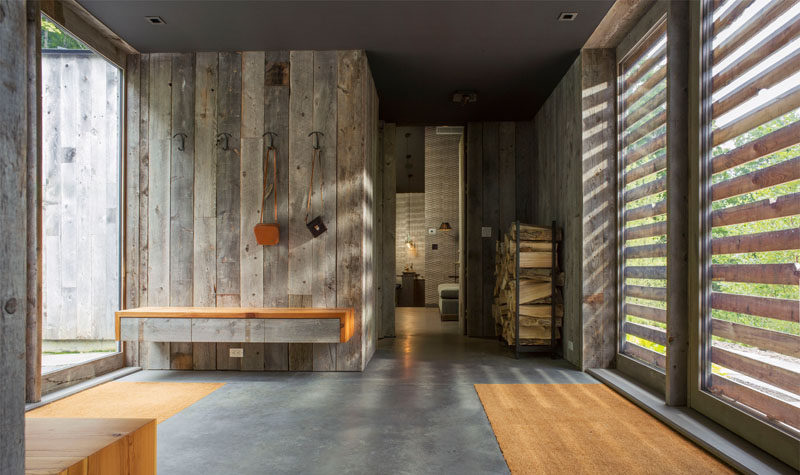 The re-purposed wood siding on the exterior of this modern house continues through to the interior, as seen here in the front entryway, that's central to the home.