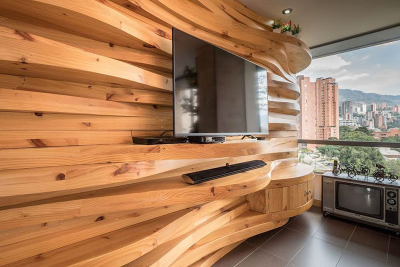 This modern apartment features a wavy wood accent wall that adds warmth to the interior, and also doubles as shelving for the television and decorative home decor items.