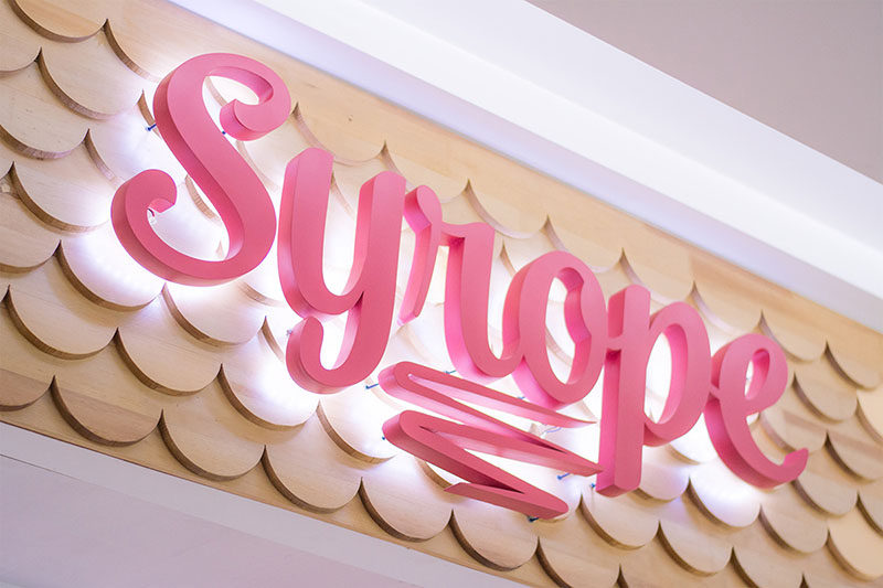 This modern retail store logo stands out from the scalloped wood facade by being slightly raised, while hidden lighting helps to highlight the business name.