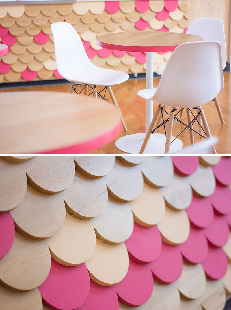 The modern furniture that sits next to this retail store has the same elements of pink, wood and white, that ties into the scalloped facade design.