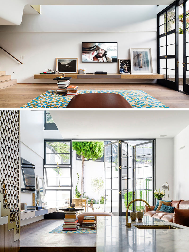 The living room in this modern house has the concrete bench from the courtyard flowing through to the interior where it becomes a floating shelf in the living room.